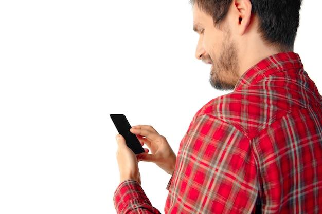 Nahaufnahme des jungen kaukasischen mannes mit mobilem smartphone mit leerem bildschirm isoliert.