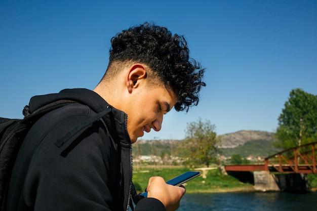 Nahaufnahme des jungen lächelnden mannes, der smartphone verwendet