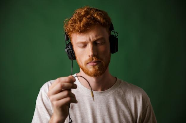 Nahaufnahme des jungen lockigen lesekopf-hipsters, der kopfhörerkabel hält, mit geschlossenen augen