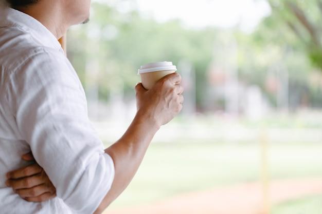 Nahaufnahme des jungen mannes, der kaffee hält, um am frühen morgen zu hause, sonnenlicht wegzunehmen