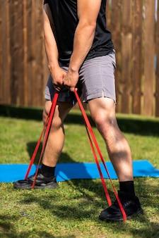 Nahaufnahme des jungen mannes geht am sommertag zu hause im hinterhof zum sport. junger sportler macht kniebeugen mit sportgummi auf matte