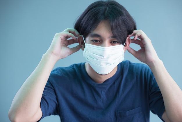 Nahaufnahme des jungen mannes in der isolierten wand der sterilen gesichtsmaske. epidemisches pandemie-coronavirus 2019, covid-19-grippevirus-konzept.