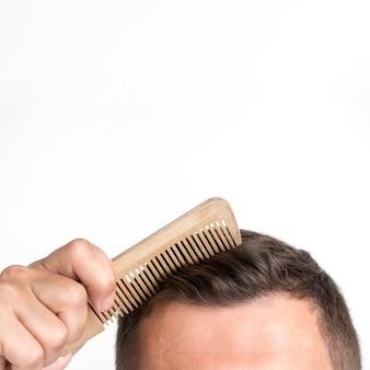 Nahaufnahme des jungen mannes kämmen sein haar gegen weißen hintergrund