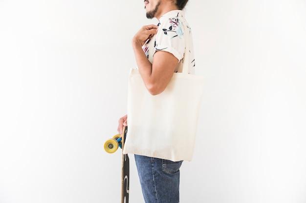 Nahaufnahme des jungen mannes mit der taschentasche, die skatingboard hält