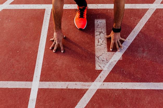 Nahaufnahme des jungen muskulösen athleten ist am anfang der rennstrecke linie im stadion. sport-konzept