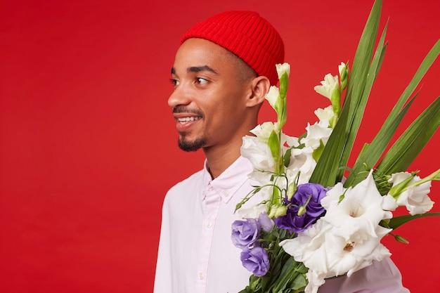 Nahaufnahme des jungen positiven dunkelhäutigen mannes, trägt in weißem hemd und rotem hut, steht über rotem hintergrund und breit lächelnd.
