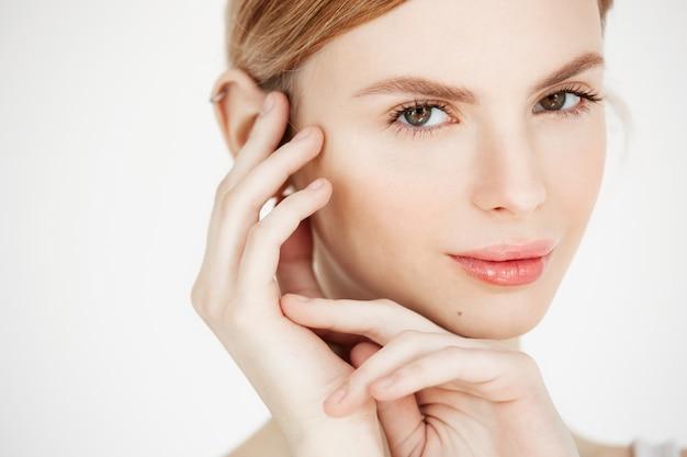Nahaufnahme des jungen schönen mädchens lächelndes berührendes gesicht. spa schönheit gesund und kosmetologie konzept.