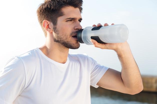 Nahaufnahme des jungen sportlers im weißen hemd trinkwasser im freien