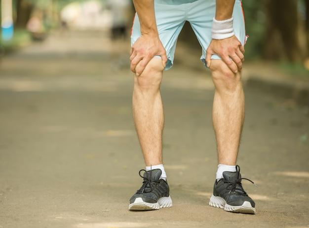 Nahaufnahme des jungen sportlichen mannes bereitet vor sich, sprint laufen zu lassen.