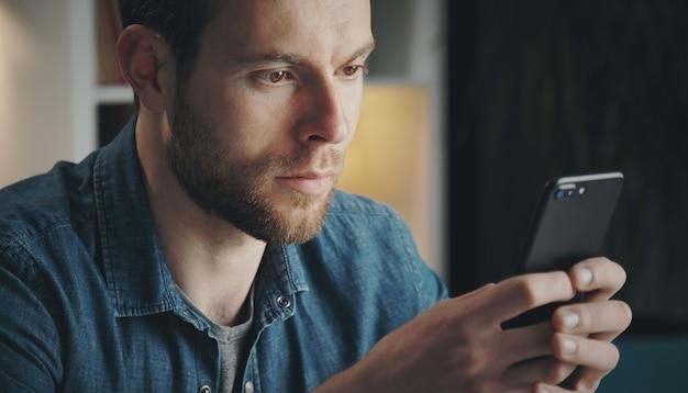 Nahaufnahme des jungen unrasierten mannes im jeanshemd, der handy mit beiden händen und sms, nach hause hält