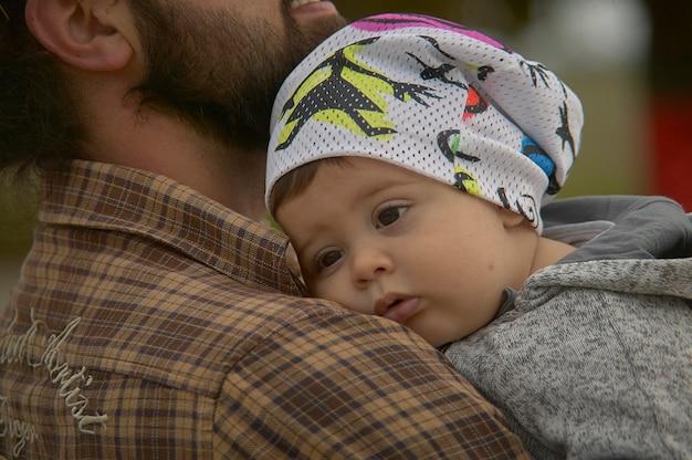 Nahaufnahme des jungen vaters hält sein baby in den armen