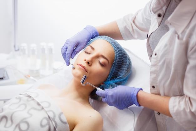 Nahaufnahme des jungen weiblichen gesichts während der mikrostromtherapie.