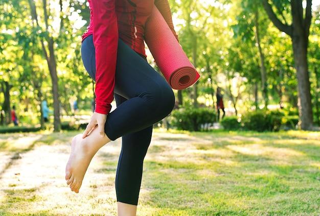 Nahaufnahme des jungen weiblichen yoga im park