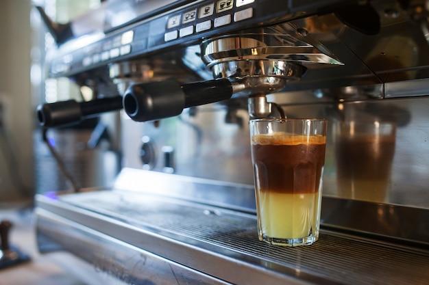 Nahaufnahme des kaffeegießens aus der kaffeemaschine. professionelle kaffeezubereitung