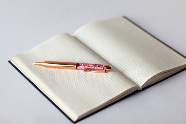 Nahaufnahme des karierten notizbuches mit goldenem rosa glänzendem stift