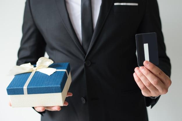 Nahaufnahme des kaufenden weihnachtsgeschenks des geschäftsmannes unter verwendung der kreditkarte