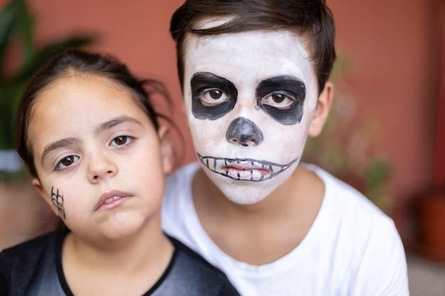 Nahaufnahme des kaukasischen jungen und des kleinen mädchens mit make-up für den tag der toten. (dia de los muertos).