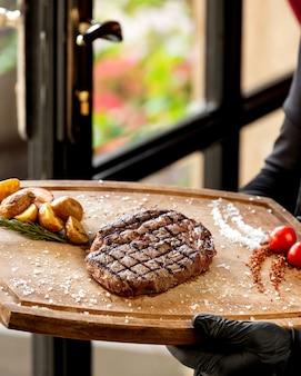 Nahaufnahme des kellners, der gegrilltes steak hält, das mit gerösteter kartoffel serviert wird
