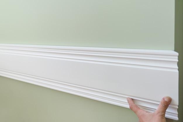 Nahaufnahme des klebens der hölzernen weißen gemalten plankenplatte auf wand