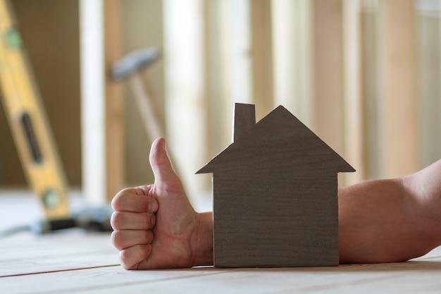 Nahaufnahme des kleinen hölzernen modellhauses auf der hand des mannes mit daumen-oben-geste und verschwommenen bildern von bauwerkzeugen. investitionen in immobilien und eigentum am traumhauskonzept.