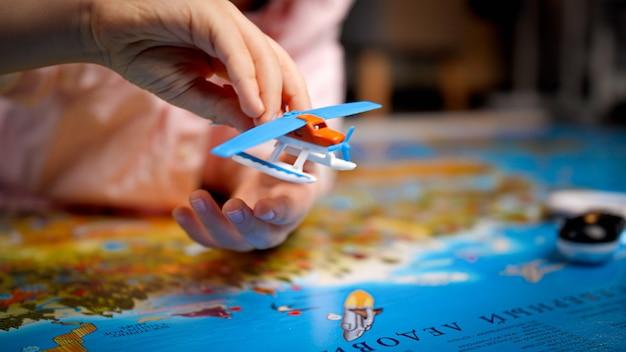 Nahaufnahme des kleinen jungen, der mit kleinem spielzeugflugzeug auf großer weltkarte spielt. konzept von reisen, tourismus und kindererziehung. kinder erkunden und entdecken.