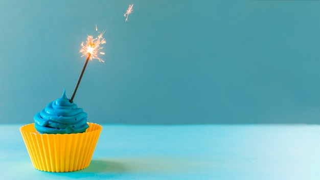Nahaufnahme des kleinen kuchens mit belichteter wunderkerze auf blauem hintergrund