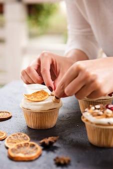 Nahaufnahme des kleinen kuchens mit zuckerglasur und getrockneter zitrusfrucht