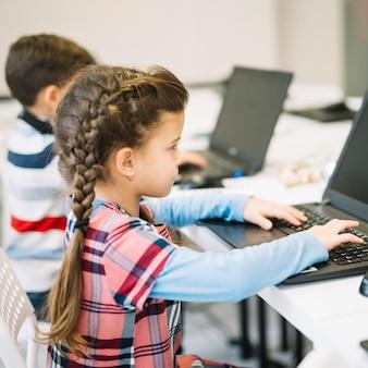 Nahaufnahme des kleinen mädchens, das laptop im klassenzimmer verwendet