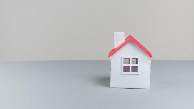 Nahaufnahme des kleinen papierhausmodells auf grauer oberfläche