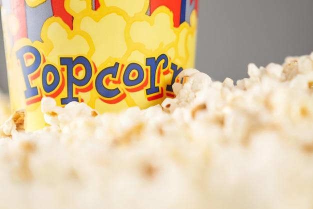 Nahaufnahme des knusprigen und frischen popcorns nahe kartonbecher. konzept des kinos.