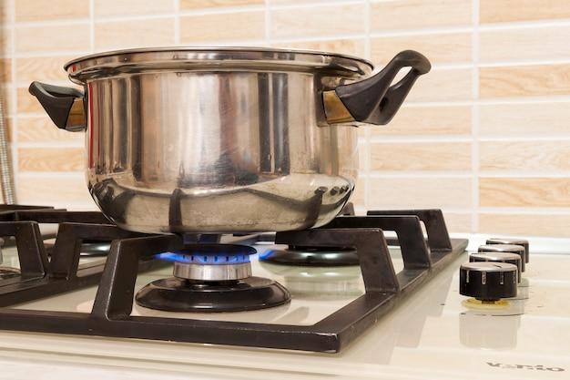 Nahaufnahme des kochenden topfes des edelstahls auf gasherd in der zeitgenössischen hochwertigen modernen hauptküche. tiefenschärfe auf topf.