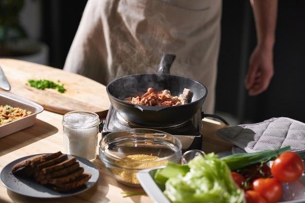 Nahaufnahme des kochs, der nahe dem herd steht und fleisch mit gemüse auf der pfanne brät