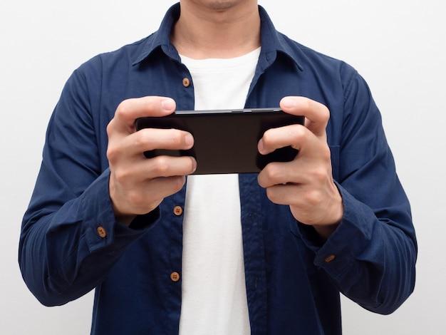 Nahaufnahme des körpers eines mannes mit handy in der handmann, der mit seinem smartphone soziale medien spielt