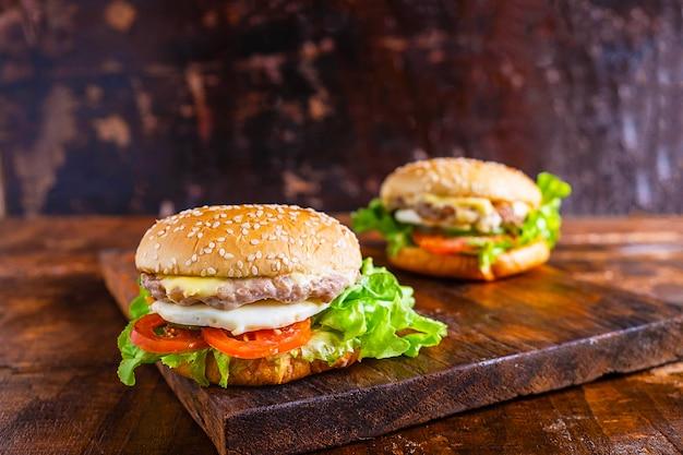 Nahaufnahme des köstlichen frischen gemachten hauptburgers mit kopfsalat, käse, zwiebel und tomate auf einer rustikalen hölzernen planke auf holztisch