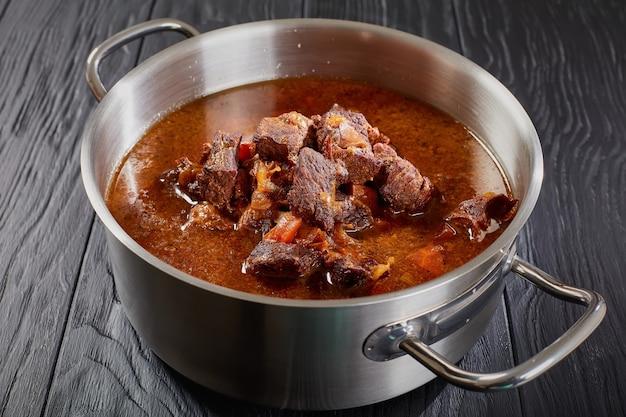 Nahaufnahme des köstlichen hausgemachten heißen traditionellen tschechischen rindergulaschs in einer rostfreien pfanne auf schwarzem holztisch