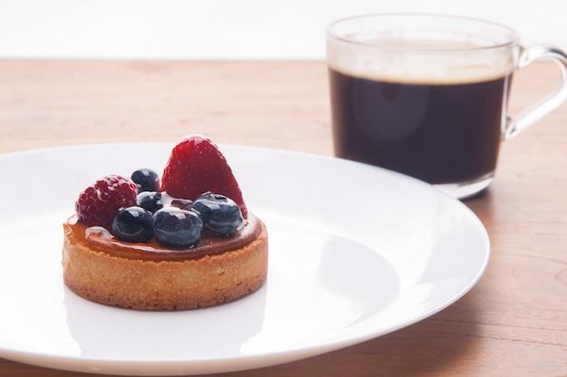 Nahaufnahme des köstlichen minitörtchens mit beeren und tasse kaffee