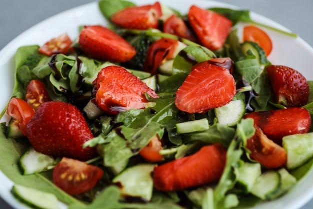 Nahaufnahme des köstlichen salats mit erdbeeren, ruccola, gurke und spinat gewürzt mit balsamico-dressing.