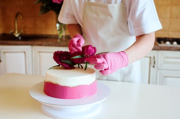 Nahaufnahme des konditors verziert appetitlichen kuchen mit pfingstrosen. drinnen in der küche. hausgemachtes dessert für den urlaub.