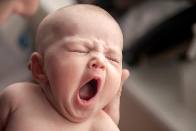 Nahaufnahme des kopfes des neugeborenen in der hand des vaters