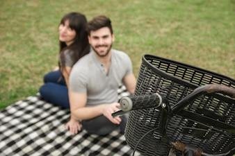 Nahaufnahme des Korbes auf Fahrrad vor den jungen Paaren, die im Park sitzen