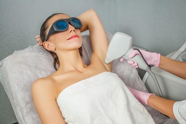 Nahaufnahme des kosmetikers haar der achselhöhle der jungen frau entfernend. laser hautpflege.