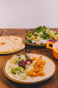 Nahaufnahme des köstlichen Maistellers mit Gemüse und Tortilla auf brauner Tabelle