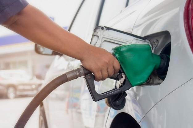 Nahaufnahme des kraftstoffüberwachungssystems, das ein erdöl zum fahrzeug an der tankstelle betankt.