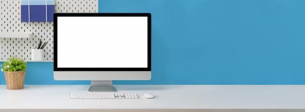 Nahaufnahme des kreativen arbeitsbereichs mit computer mit leerem bildschirm, verbrauchsmaterial und kopierraum auf weißem tisch