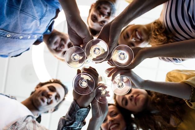 Nahaufnahme des kreativen geschäftsteams, das einen toast am collegegeburtstag im büro hat
