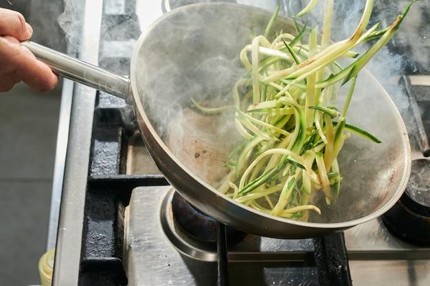 Nahaufnahme des küchenchefs, der zucchini-spaghetti über einem sehr heißen dampfenden wok kocht
