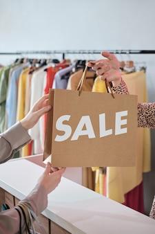 Nahaufnahme des kunden, der die papiertüte vom verkäufer nimmt, während er während des verkaufs einen kauf tätigt