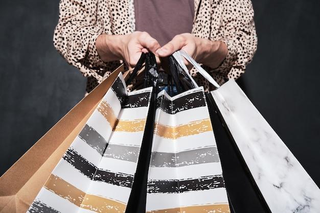 Nahaufnahme des kunden, der einkaufstüten mit einkäufen in den händen hält, isoliert auf schwarzem hintergrund