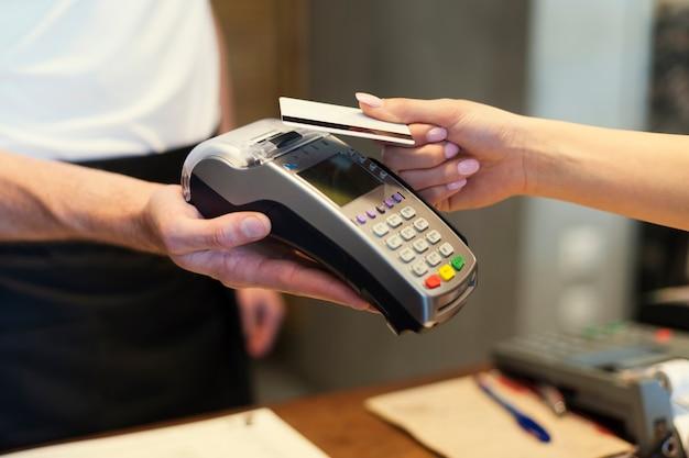 Nahaufnahme des kunden, der mit kreditkarte bezahlt