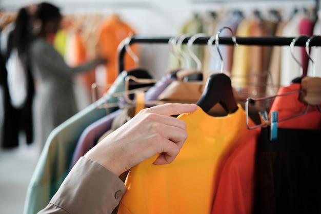Nahaufnahme des kunden, der neue kleidung auf dem regal im laden auswählt